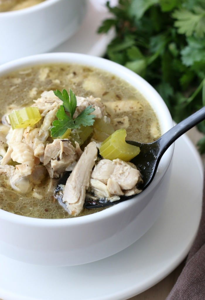 A spoon full of delicious chicken soup ready to be enjoyed.