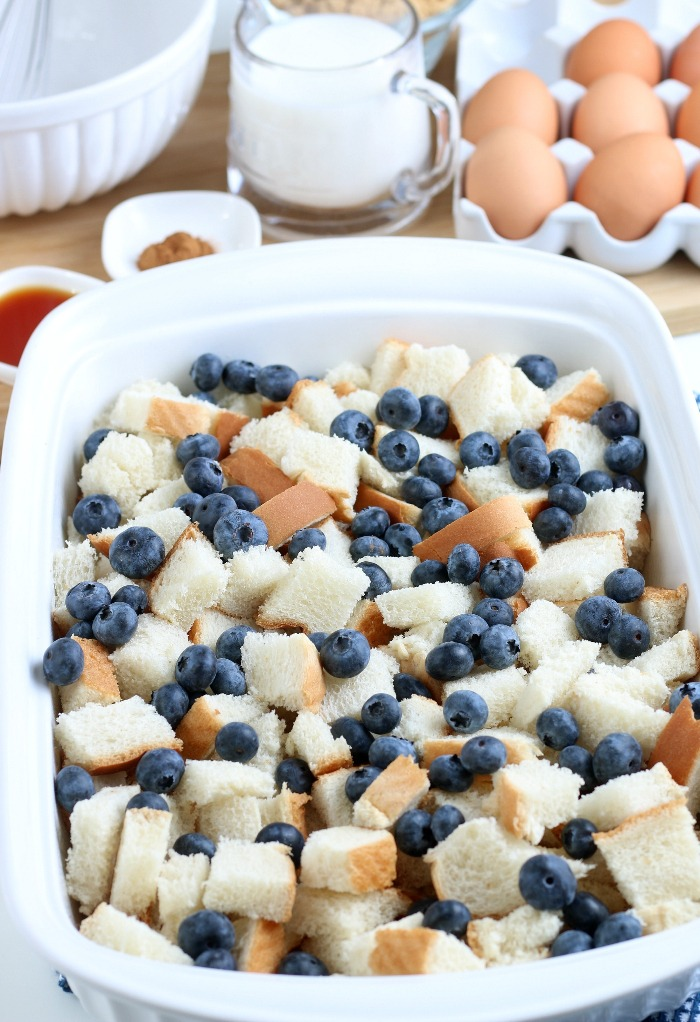 Here we see the start of our french toast casserole, bread and berries being added to the casserole dish.