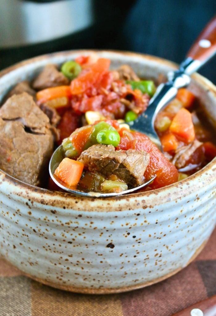 A bowl of beef vegetable soup wit a spoon digging in