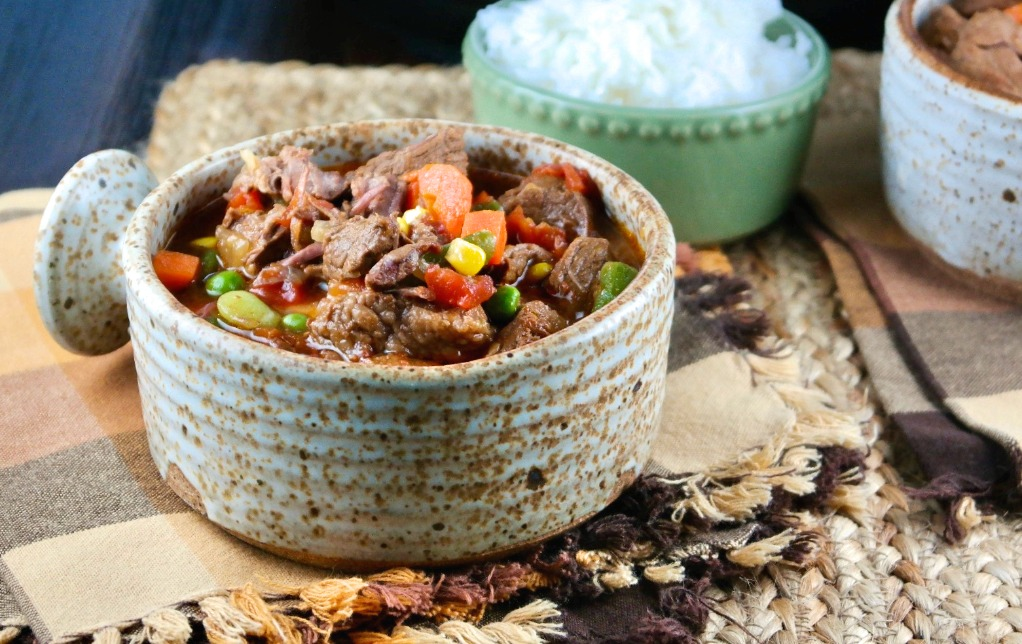A soup bowl filled with beef and vegetables with a side dish of rice.