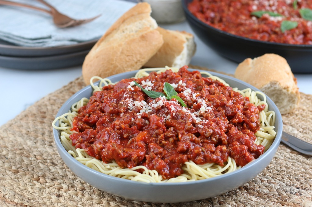Here we see a horizontal view of a full dish of pasta with red meat sauce on top!