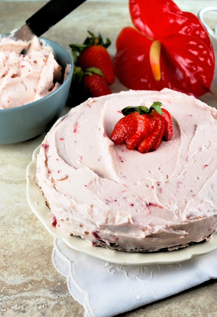 Sugar free cake topped with buttercream strawberry frosting on a white plate ready to be sliced.