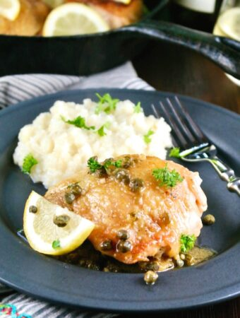 Black plate of low carb chicken piccata and mashed cauliflower