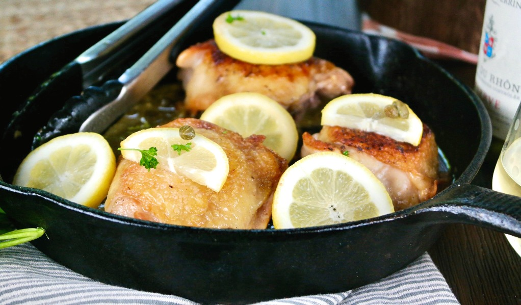 horizontal view of chicken piccata made with thighs in a iron skillet