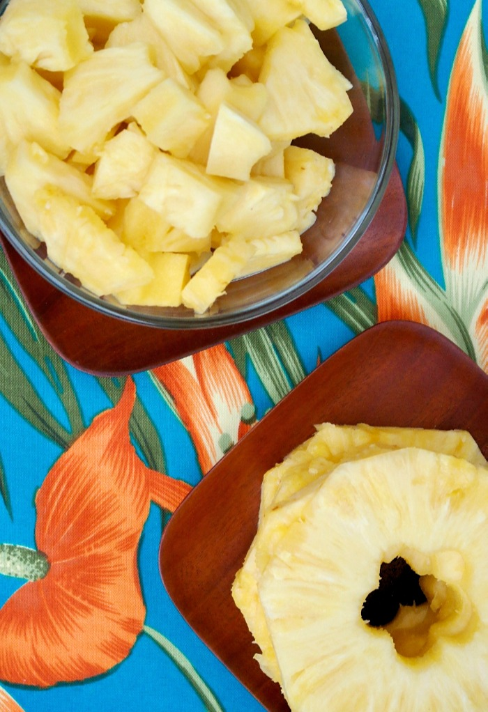 Fresh sliced pineapple and pineapple chunks on brown wooden plates.