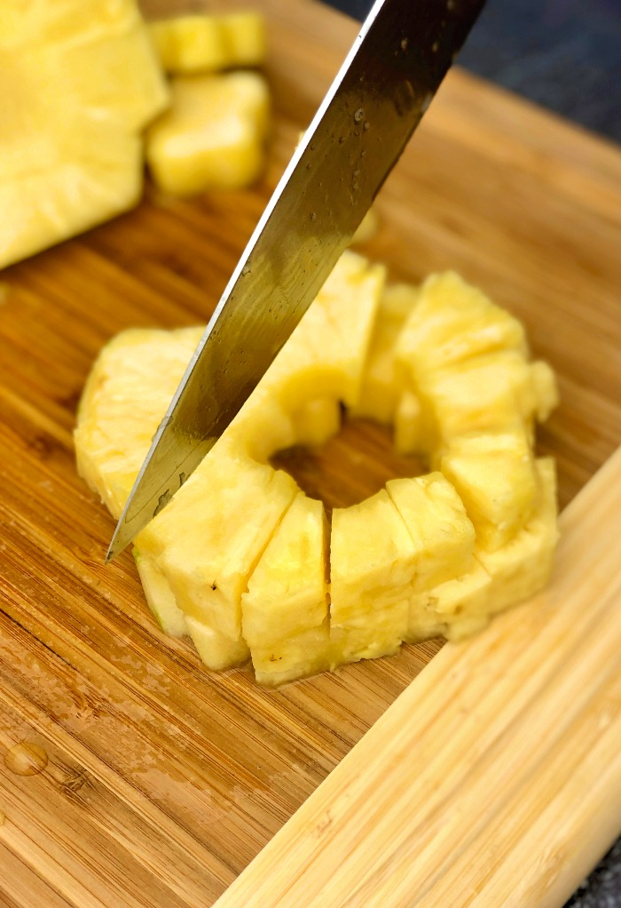 Cutting pineapple rings into chunks
