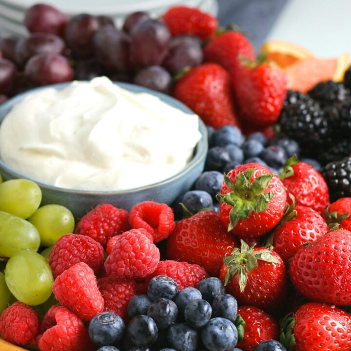 cream cheese fruit dip in a blue bowl surrounded with fresh fruit