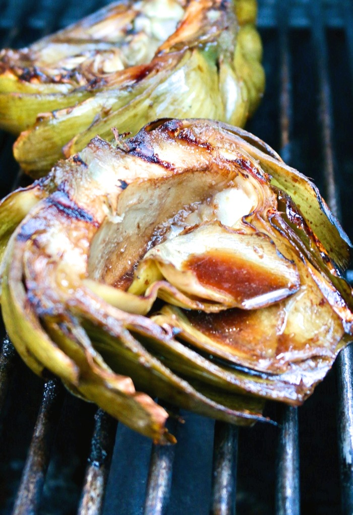Half artichokes on a grill finishing cooking
