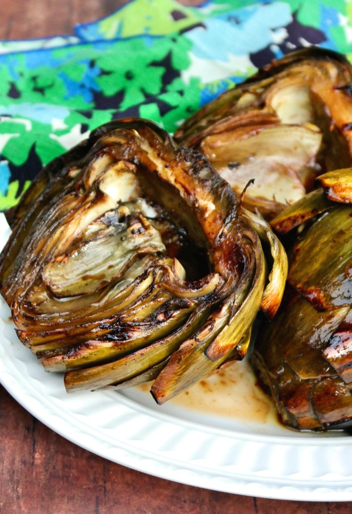 Cooked artichokes on a white platter