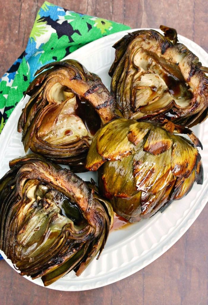 Large globe artichokes grilled and placed on a white platter