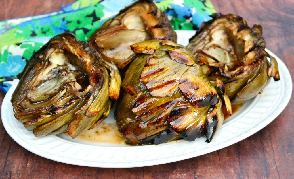 Horizontal view of cooked artichokes on a white serving platter.