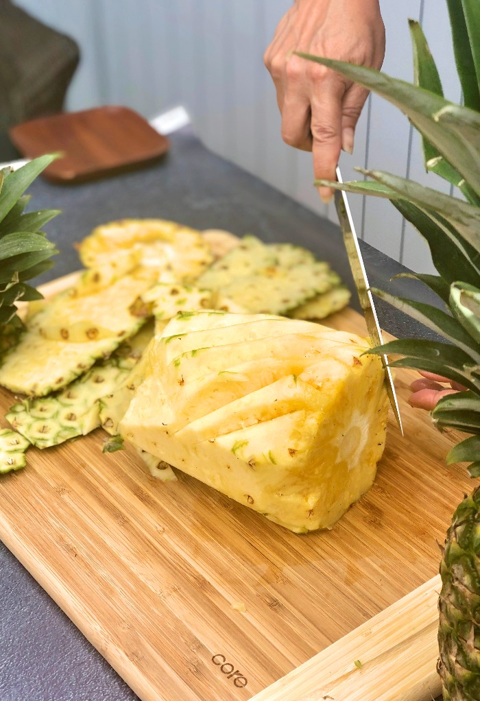 Photo of fresh pineapple cutting in V to remove the eyes