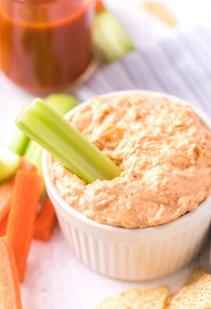 A white bowl with keto buffalo chicken dip with celery.