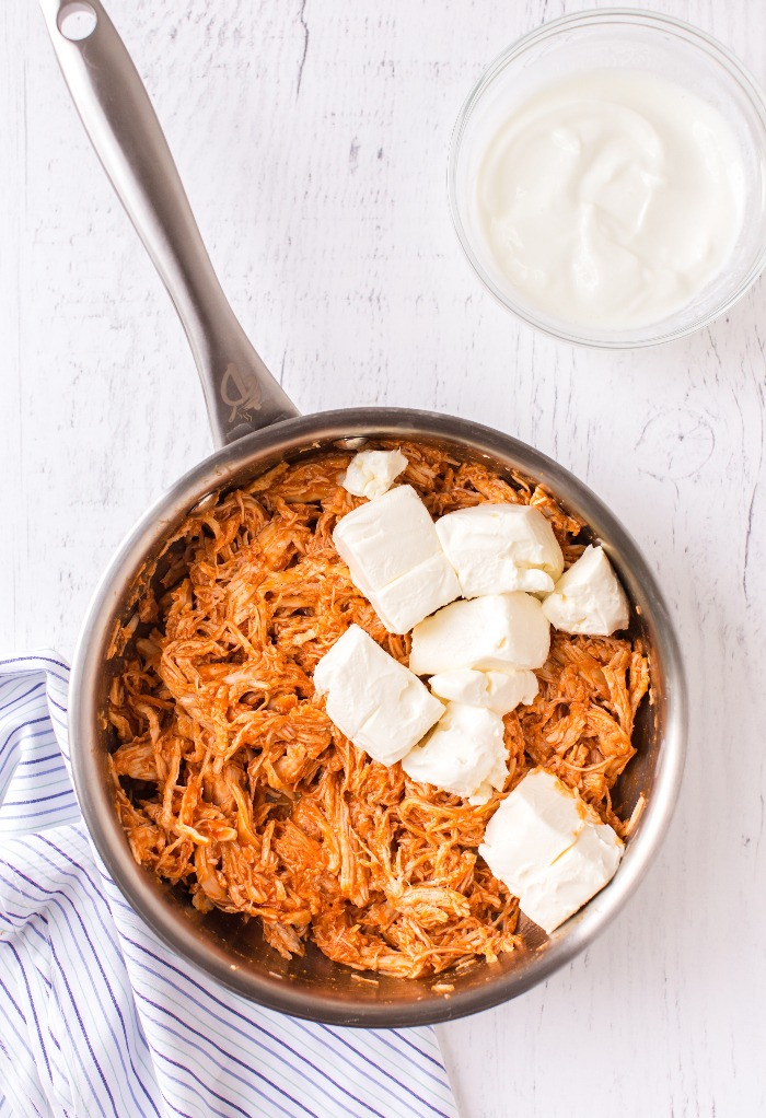 Here is a sauce pan with shredded chicken and cream cheese.