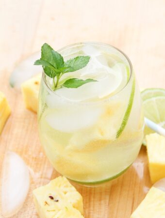 Pineapple mojito in a clear glass with a sprig of mint