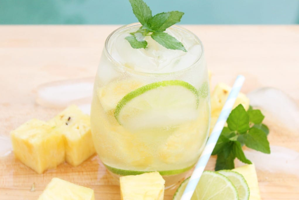 clear glass with chunks of pineapple around a pineapple mojito cocktail.