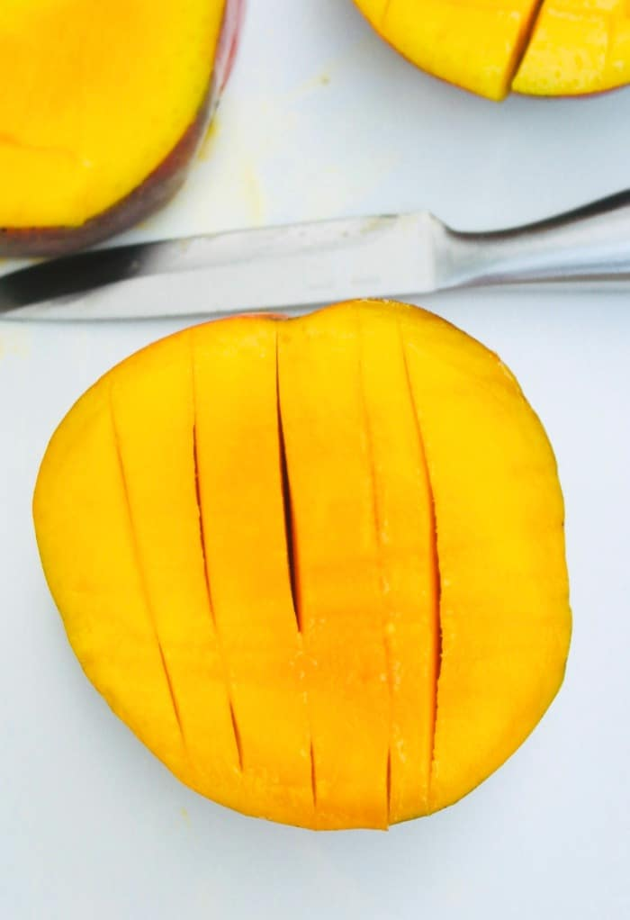 A half of a mango with vertical slices cut into the manto.