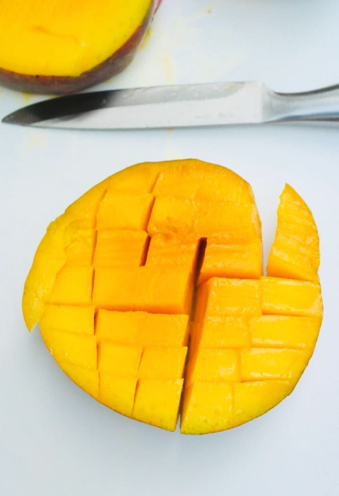 A cut mango with vertical and horizontal slices in a mango.