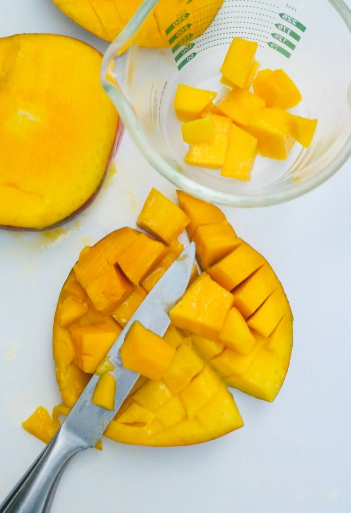Removing cut mango with a knife.