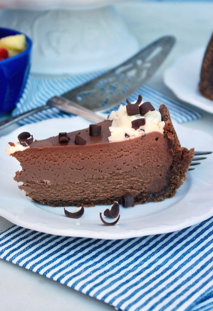 Slice of keto chocolate cheesecake on a white plate with a blue and white stripped napkin