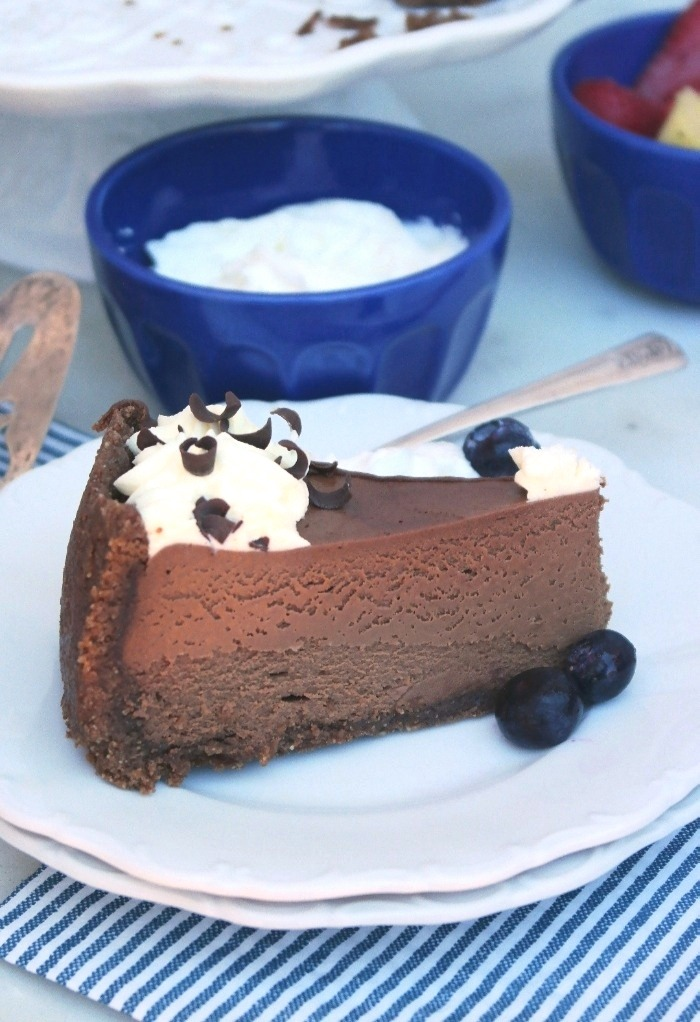 Large slice of chocolate cheesecake on a white plate with a blue bowl of whipped cream in the back.