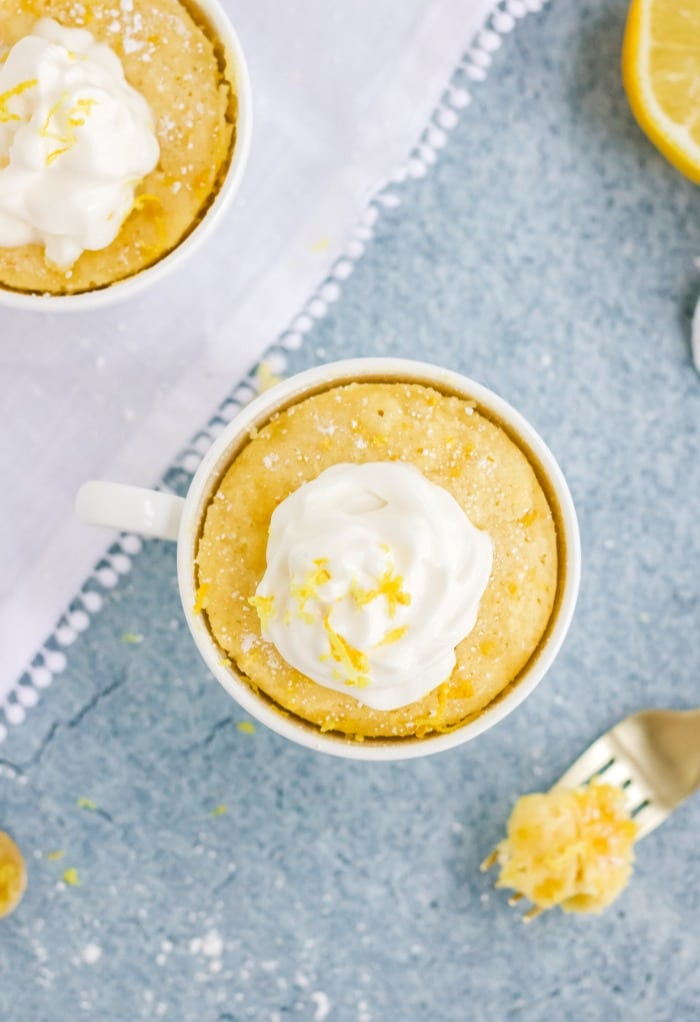 Overhead view of keto lemon mug cakes topped with whipped cream and a sprinkle of lemon zest.