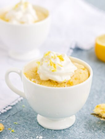 Keto lemon mug cake in a white mug topped with whipped cream.