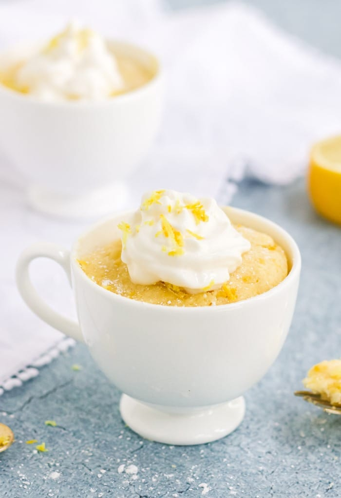 Keto lemon mug cake in a white mug topped with whipped cream.