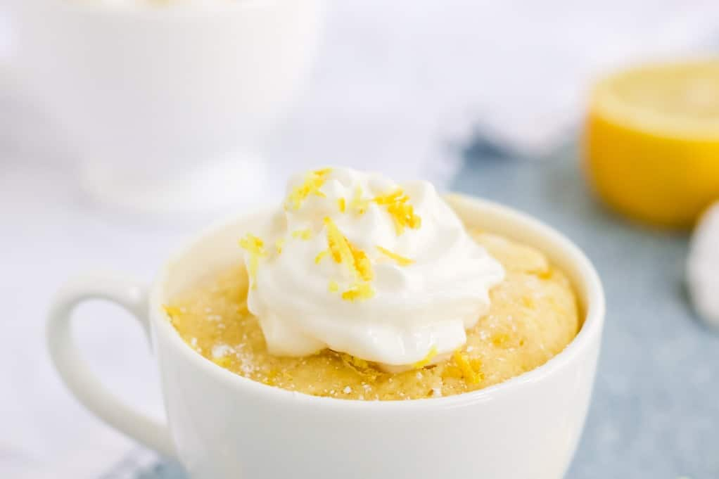 Close up view of keto lemon mug cake in a white mug topped with fresh whipped cream.