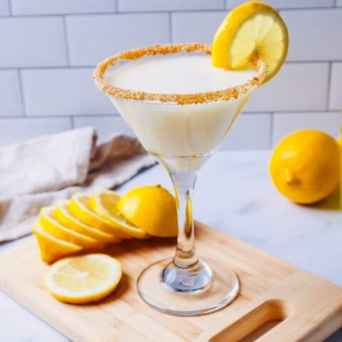 Horizontal view of limoncello martini on a cutting board with sliced lemon