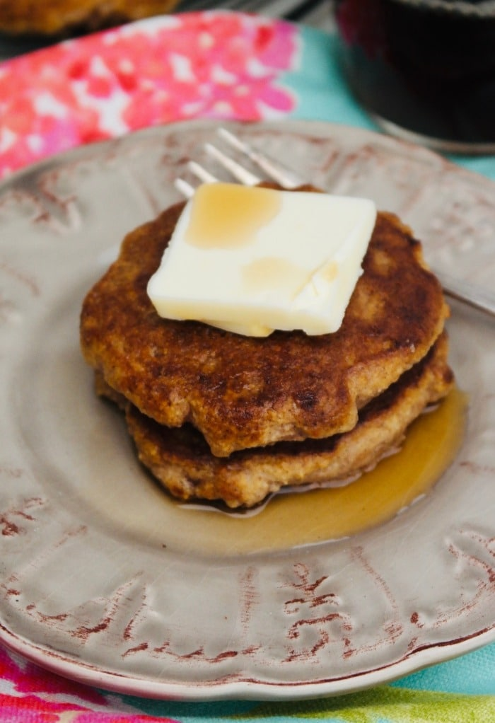 Cinnamon pancakes with butter and syrup on a tan plate.