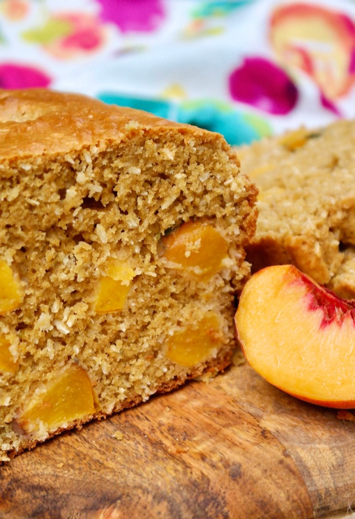 Homemade peach bread with a slice of fresh peach on the side.
