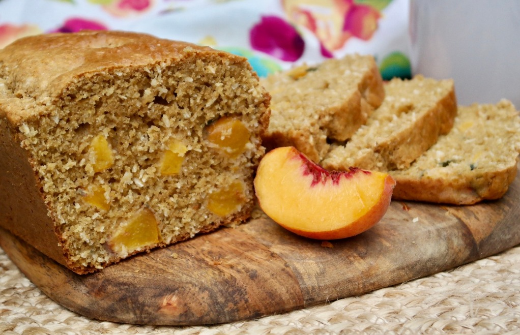 A loaf of peach bread on a cutting board with a slice of fresh peach on the side