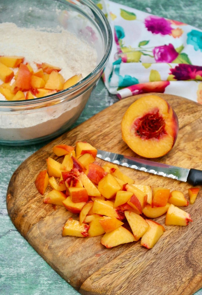 Fresh diced peaches on a cutting board.