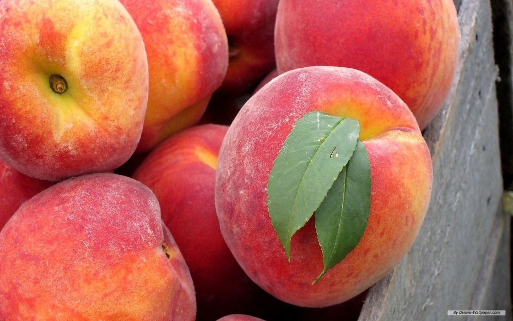 Photo of fresh peaches in a wooden crate