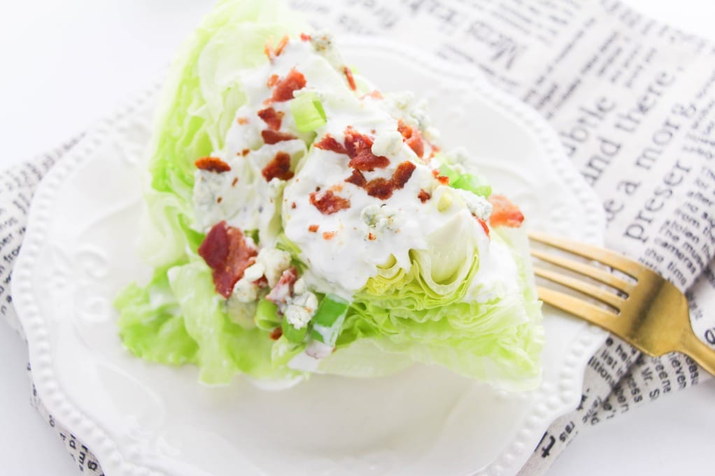Wedge salad with dressing on a white plate.
