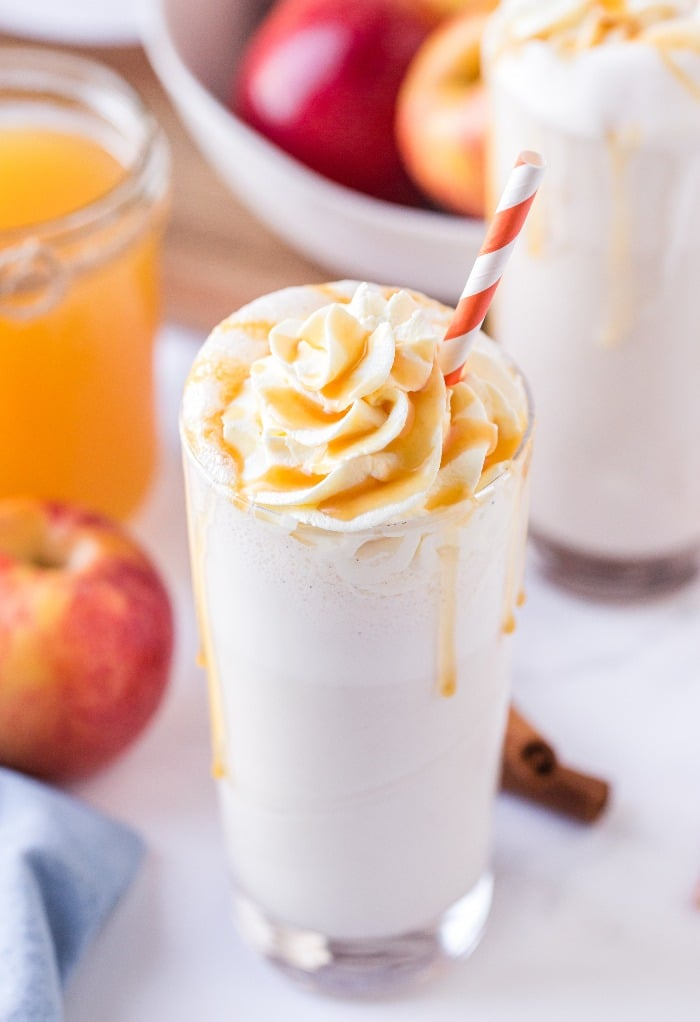 Homemade apple milkshake in a clear glass topped with whipped cream.