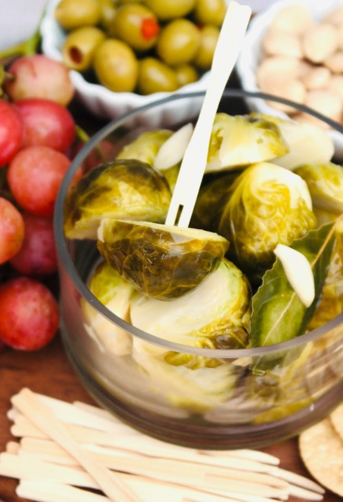 Pickled brussels sprouts in a glass bowl surrounded by grapes and olives to be enjoyed.