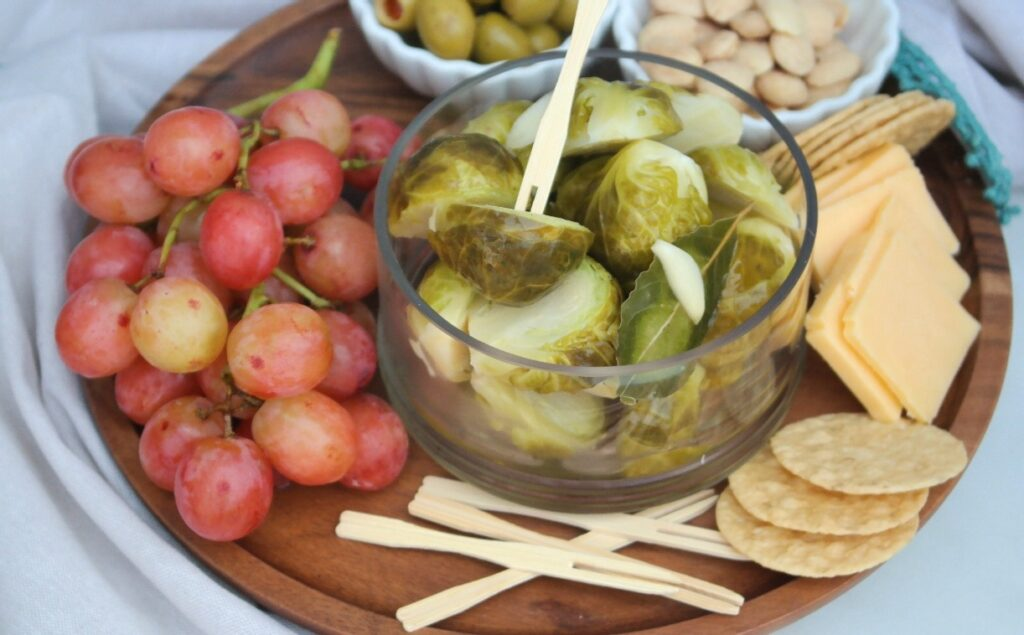 Wooden plate with appetizers like cheese and crackers ready to be eaten.