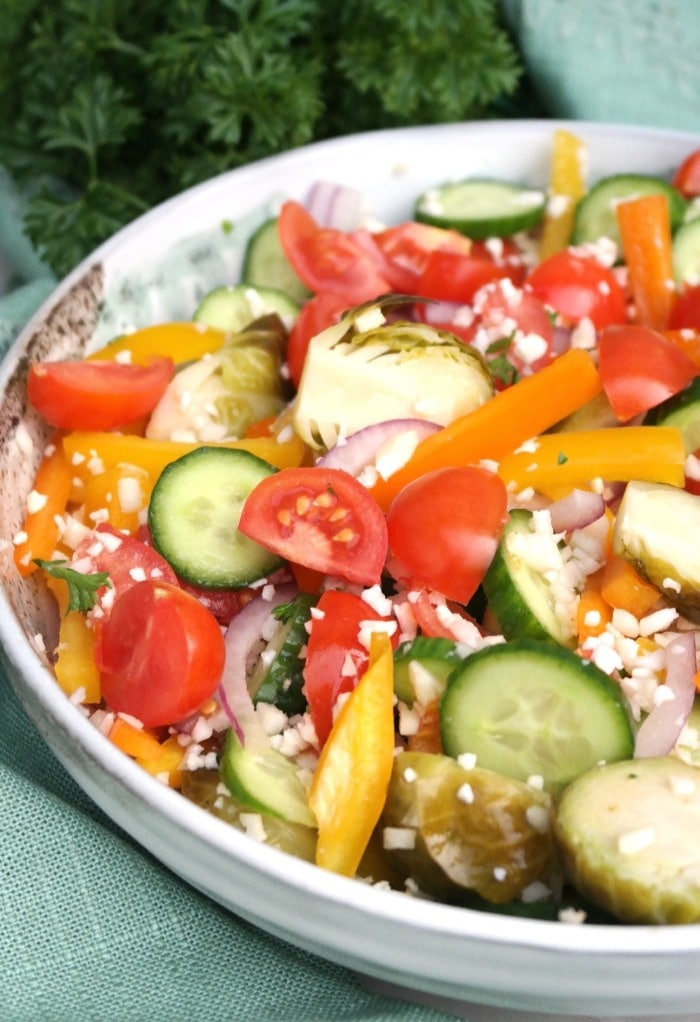 A large salad bowl filled with cauliflower rice and vegetables.