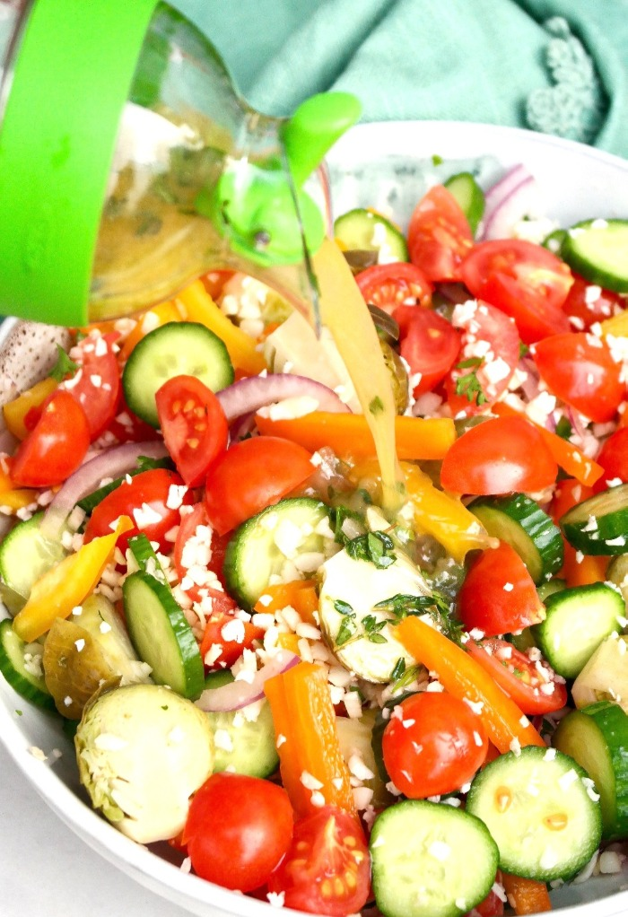 Pouring Greek dressing a bowl filled with vegetables.