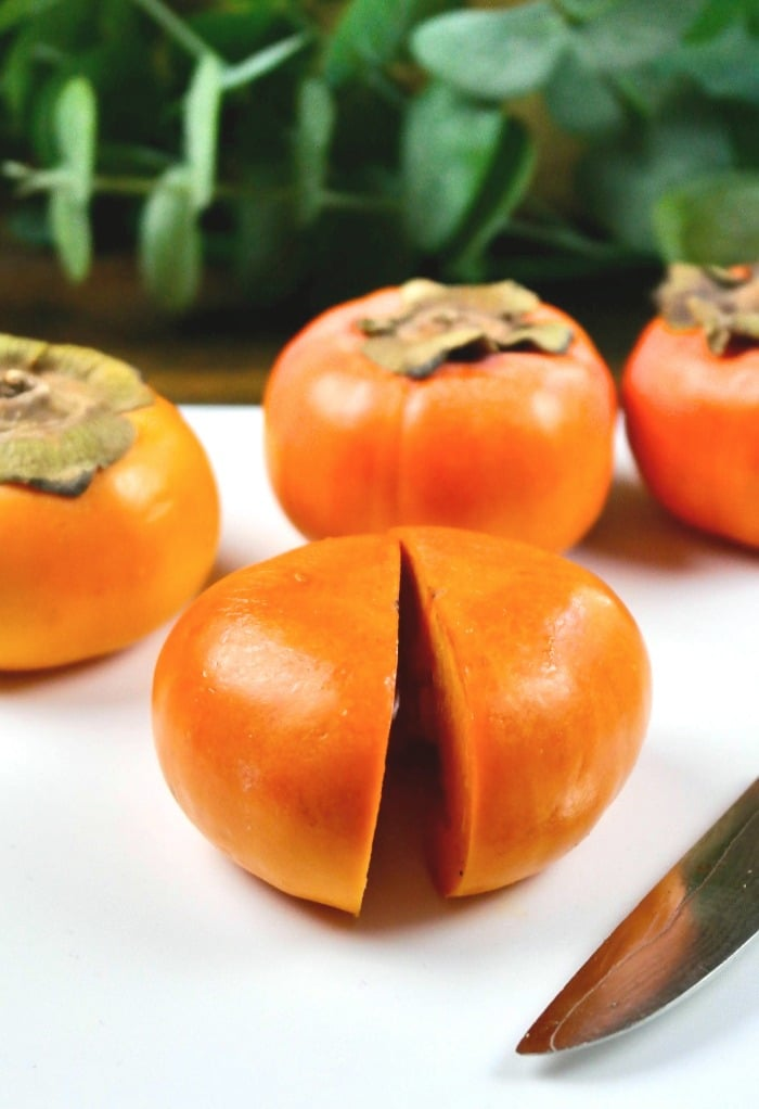 Slice the persimmon in half on a white cutting board.