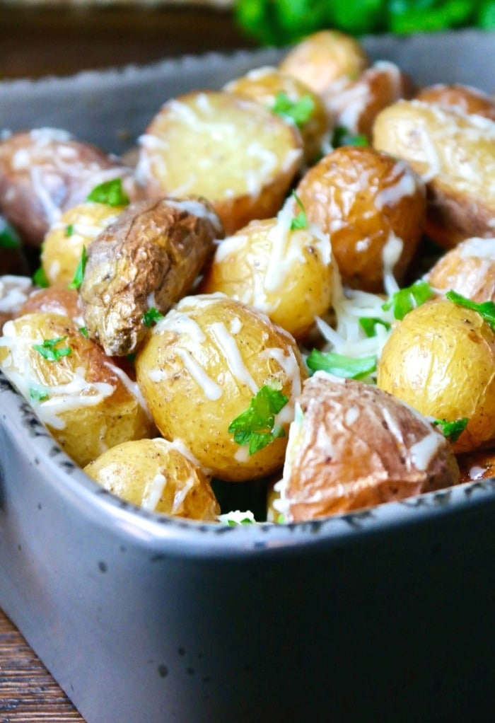 Baby potatoes with parmesan cheese in a gray serving dish.