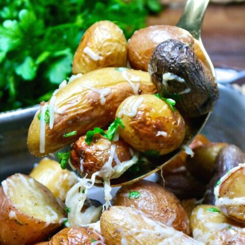 A spoonful of roasted fingerling potatoes ready to be served.