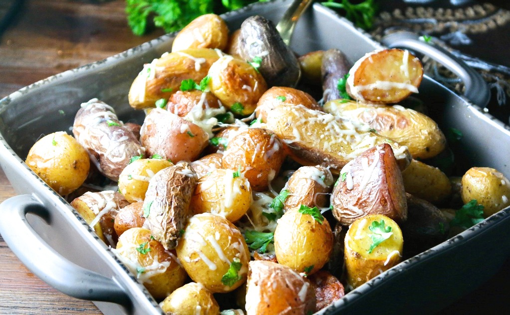 A horizontal view of cooked baby potatoes in a serving dish.