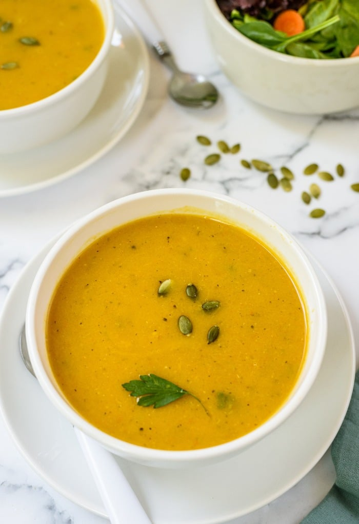 Fresh butternut squash soup in a white bowl with a green salad on the side.
