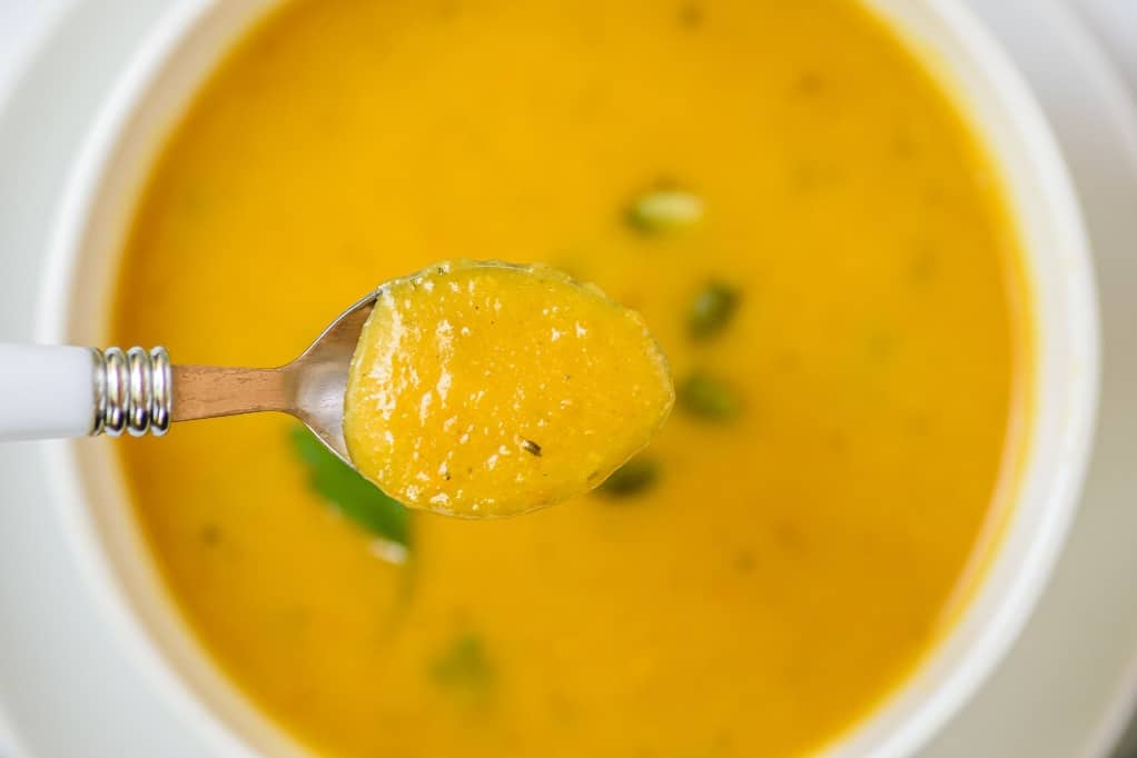 A close up view of a spoonful of butternut squash soup.