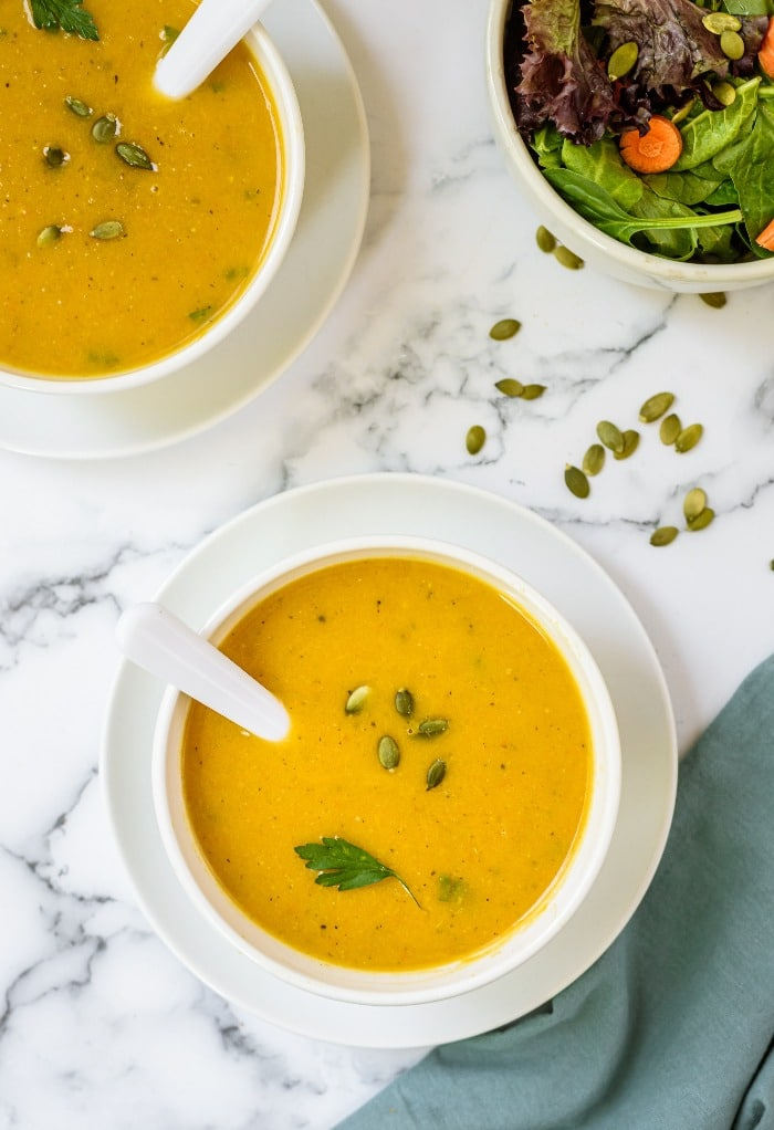 White bowls of butternut squash soup topped with pumpkin seeds.