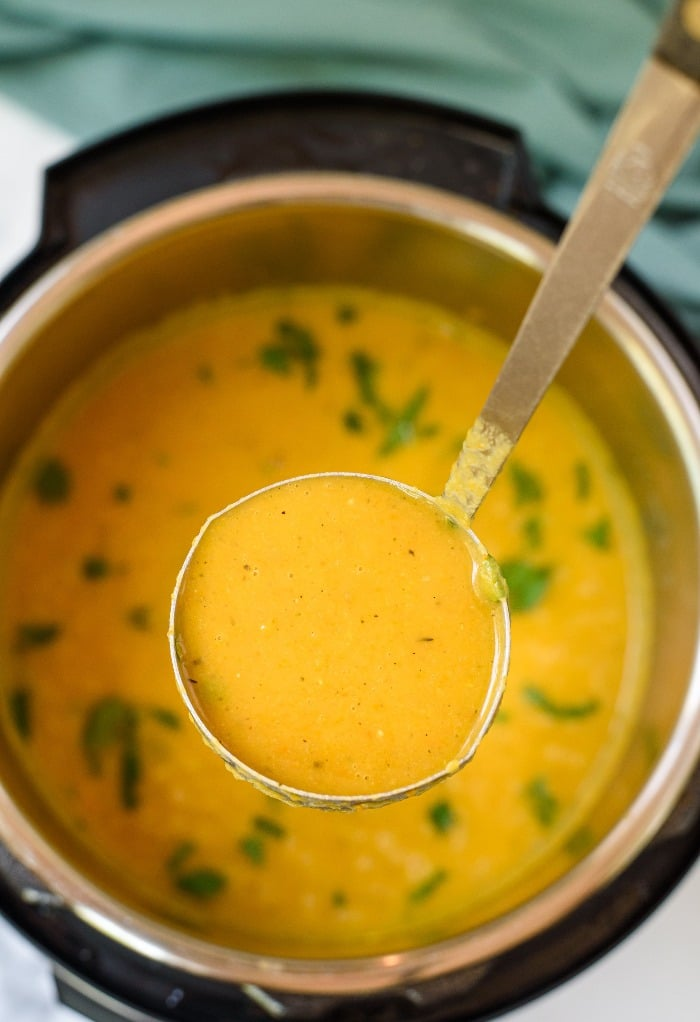 A ladle full of butternut squash soup made in an Instant Pot.