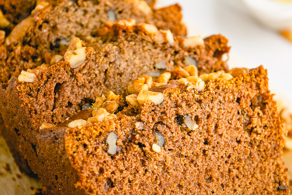Close up view of sliced persimmon bread with nuts.
